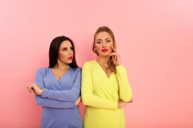 Prachtige heldere dames in stijlvolle zomerjurken, geel en blauw. blond en brunette met grote rode lippen en modern kapsel. welgevormde hete lichamen, sexy modellen. schieten in de studio op de achtergrond van de pin Gratis Foto