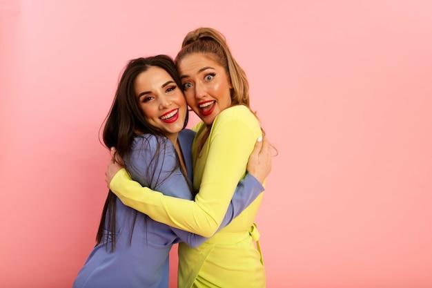 Prachtige heldere dames in zomerse stijlvolle jurken, geel en blauw. blond en brunette met grote rode lippen en modern kapsel. welgevormde hete lichamen, sexy modellen. schieten in de studio op de achtergrond van de pin