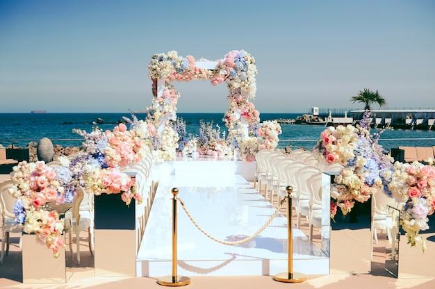 Prachtige huwelijksceremonie plaats in de buurt van de zee versierd met bloemen