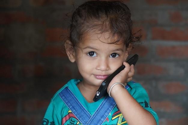 Prachtige indiase baby meisje kind gezicht met behulp van mobiel