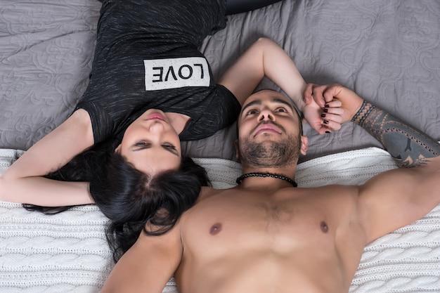 Prachtige internationale paar man met blote borst en brunette vrouw liggend op het grijze gezellige bed in de slaapkamer