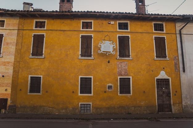 Prachtige italiaanse architectuur in een klein dorpje in het noorden van het land. oud huis met een armoedige oranje gevel, ramen gesloten met houten luiken en een getraliede deur in het dorp padernello.