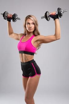 Prachtige jonge atletische vrouw met chromen halters in haar handen sporten.