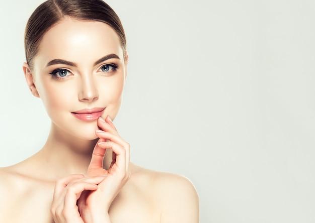 Prachtige, jonge, bruinharige vrouw met schone huid en delicate make-up raakt het gezicht.