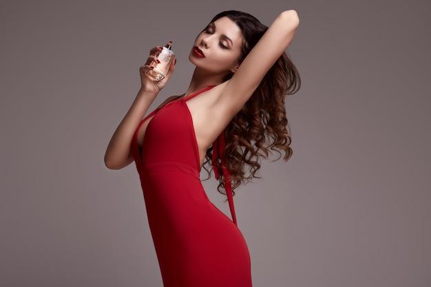 Prachtige jonge brunette vrouw met krullend haar in rode jurk