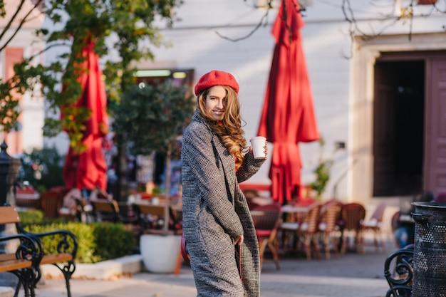Prachtige jonge dame in vintage grijze jas over schouder kijken op café achtergrond wazig