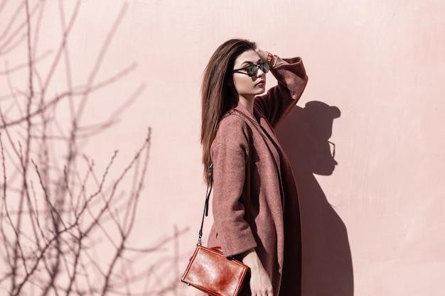Prachtige jonge fashion model stijlvolle meisje in zonnebril in jas met handtas raakt haar in de buurt van roze muur in straat. mooi meisje in elegante outfit poseert buiten in de stad op zonnige dag. retro.