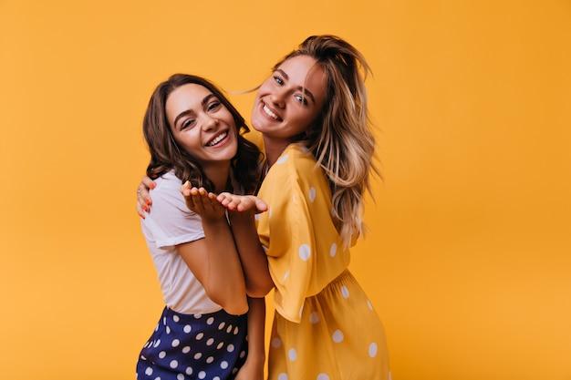 Prachtige jonge meisjes die gelukkige emoties uitdrukken. binnenportret van fascinerende witte vrouwelijke modellen die zich op geel bevinden.