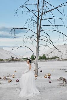 Prachtige jonge model bruid in een modieuze trouwjurk poseren in de zoute woestijn op een zomerse dag