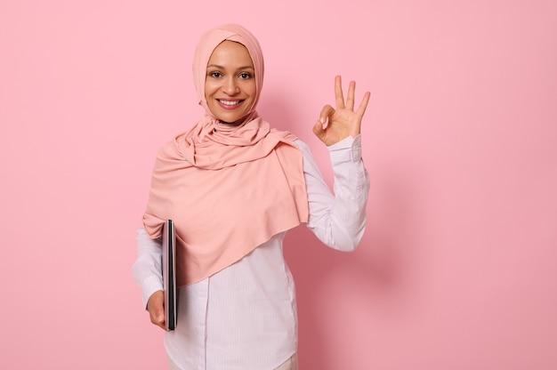 Prachtige jonge moslimvrouw van midden-oosterse etniciteit die een laptop onder de armen houdt en een ok-teken met vinger toont, glimlacht met een brede glimlach die naar camera kijkt, roze achtergrondkopieerruimte