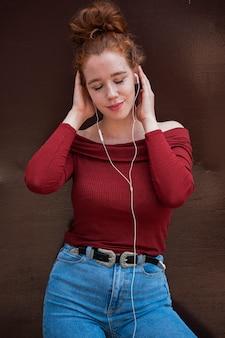 Prachtige jonge vrouw die aan muziek luistert