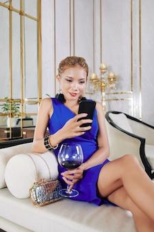 Prachtige jonge vrouw die haar tijd doorbrengt met het drinken van rode wijn en het controleren van sociale media