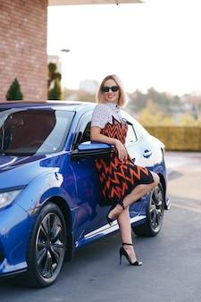 Prachtige jonge vrouw draagt jurk poseren voor haar auto buitenshuis, eigenaarsbestuurder