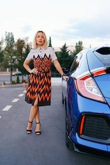 Prachtige jonge vrouw gekleed in jurk poseren voor haar auto op de weg met lucht op de achtergrond, eigenaarsbestuurder