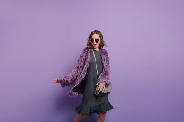 Prachtige jonge vrouw grappig dansen met oprechte glimlach op paarse achtergrond