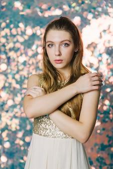 Prachtige jonge vrouw in avondjurk poseren op sprankelende achtergrond. meisje in een avondjurk op een glanzende achtergrond