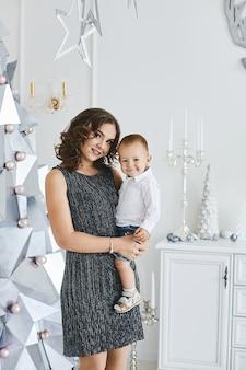 Prachtige jonge vrouw in een modieuze jurk poseren met haar schattige zoontje in het interieur versierd voor kerstmis