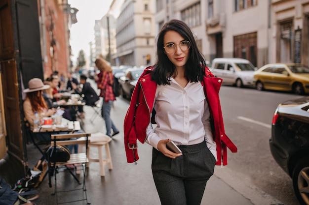 Prachtige jonge vrouw in formele kleding die op straat loopt