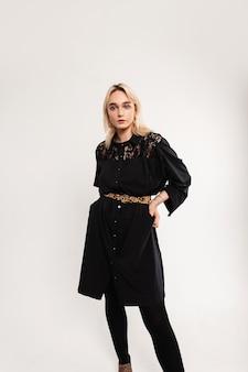 Prachtige jonge vrouw in lange modieuze mooie zwarte jurk met vintage luipaard riem staat in de buurt van witte muur. aantrekkelijke mooie stijlvolle meisje in elegante outfit poseren binnenshuis. schoonheidsdame