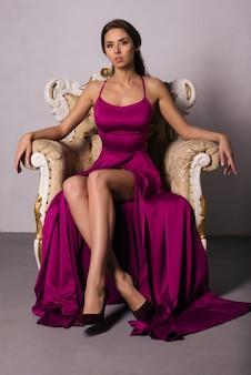 Prachtige jonge vrouw in luxe jurk zit in een stoel