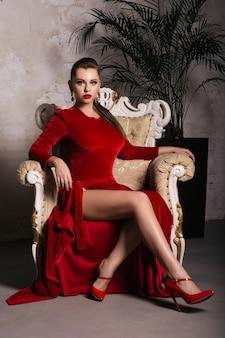 Prachtige jonge vrouw in luxe rode jurk