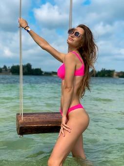 Prachtige jonge vrouw in roze zwembroek staat in de buurt van de schommel aan zee. zomervakantie aan de zee van mooie dame