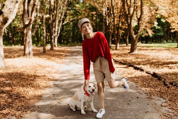 Prachtige jonge vrouw in trendy rode trui en beige korte broek met plezier in het prachtige herfstpark met haar hond.