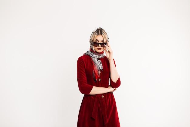 Prachtige jonge vrouw mannequin opstijgt zonnebril binnenshuis. chique blond meisje met modieuze luipaard sjaal op hoofd met mooie lippen in stijlvolle bordeauxrode jurk poseren. retro-outfit.