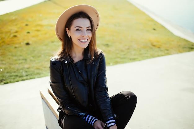 Prachtige jonge vrouw meisje, zittend in het park in de buurt van het stadsmeer in koude zonnige zomerdag gekleed in zwarte kleding