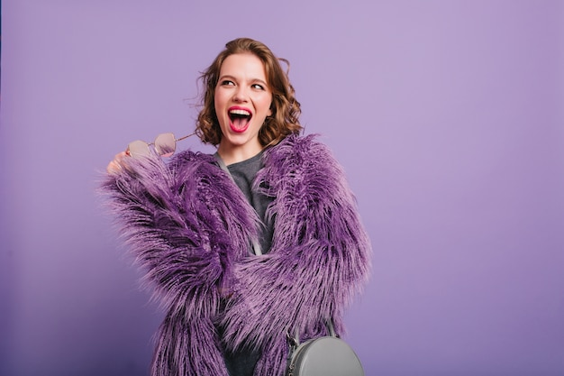 Prachtige jonge vrouw met een gelukkige glimlach die zich voordeed op heldere paarse achtergrond