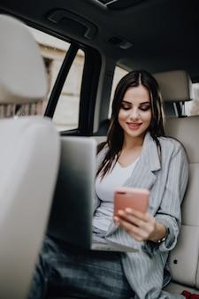 Prachtige jonge vrouw met laptop in de auto zitten en praten over de telefoon