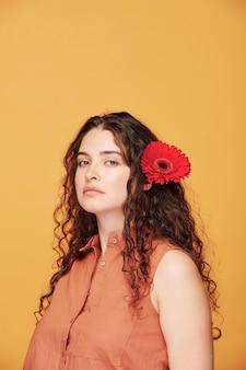 Prachtige jonge vrouw met rode herbera in haar mooie donkere lange golvende haar die naar je kijkt terwijl ze poseren over gele muur