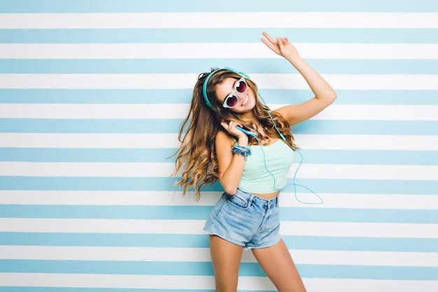 Prachtige jonge vrouw met stijlvolle tank-top en zonnebril plezier thuis, favoriete liedje luisteren. portret van aantrekkelijk vrolijk meisje dansen in denim shorts met handen omhoog.