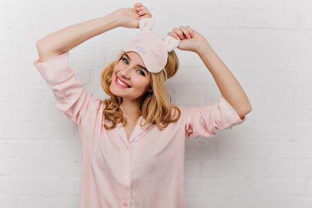 Prachtige jonge vrouw met trendy kapsel die zich uitstrekt in de ochtend. leuk meisje in roze eyemask positieve emoties uitdrukken.