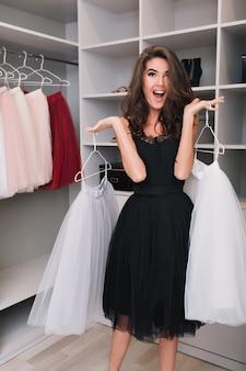 Prachtige jonge vrouw met vrolijke blik met mooie witte pluizige rokken in een grote mooie kleerkast, aangenaam verrast, geschokt, opgewekt. modieus model met zwarte jurk, elegante look.