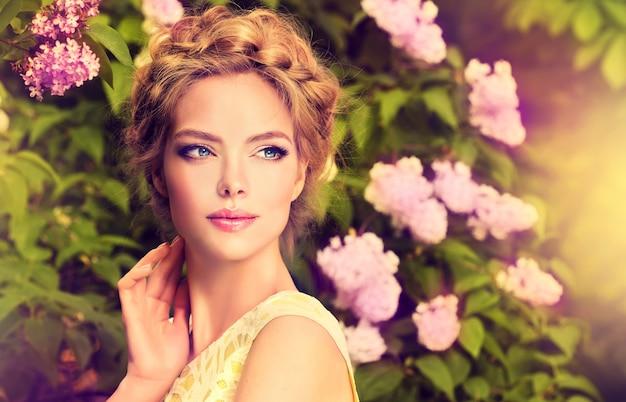Prachtige jonge vrouw omringd door bloeiende bloembomen.