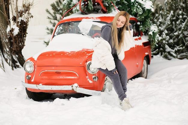 Prachtige jonge vrouw poseren in de buurt van een retro rode auto in de winter