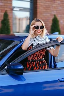 Prachtige jonge vrouw waring jurk poseren voor haar auto buitenshuis, eigenaarsbestuurder