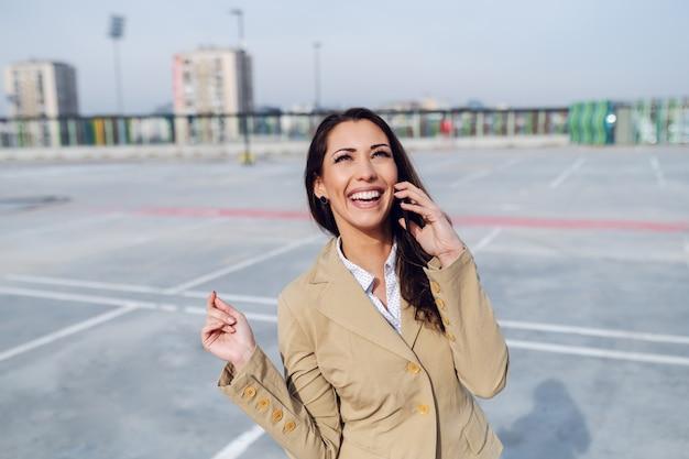 Prachtige kaukasische brunette gekleed in beige jas staande op parkeerplaats en met behulp van slimme telefoon om taxi te bellen.