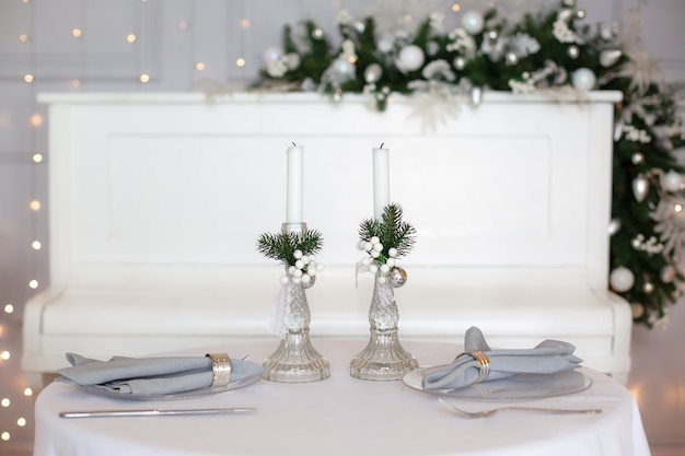Prachtige kerstdiner instelling. feestelijke tafel instelling met een tafelkleed tussen winter decoraties en witte kaarsen. bovenaanzicht, platliggend. het concept van kerstmis of thanksgiving-familiediner.