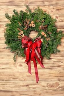 Prachtige kerstkrans gemaakt door professionele bloemist op houten tafel