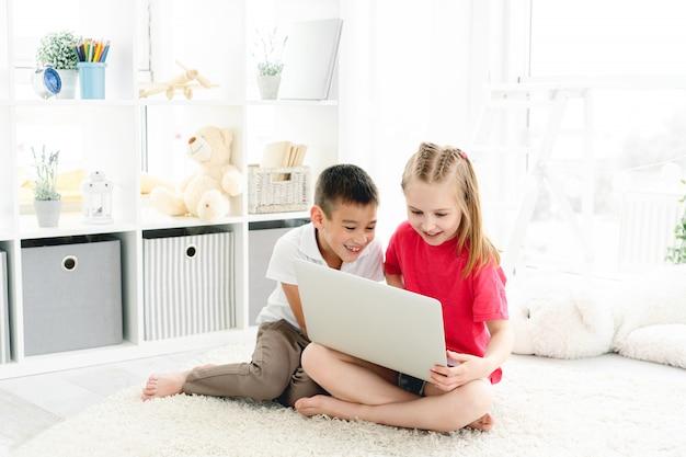 Prachtige kinderen met behulp van laptop in de kamer