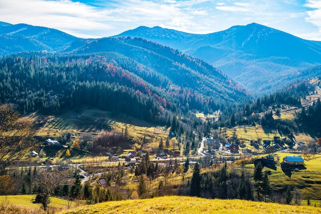Prachtige kleurrijke bossen die de karpaten bedekken en een klein dorp tegen de achtergrond van een warme herfstlucht