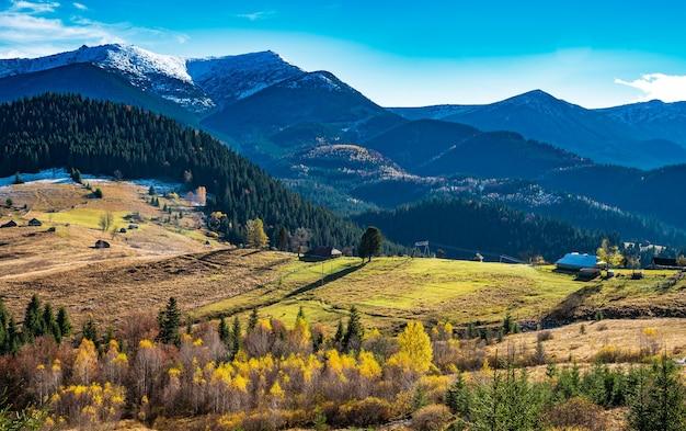 Prachtige kleurrijke bossen die de karpaten bedekken en een klein dorpje ertegenover