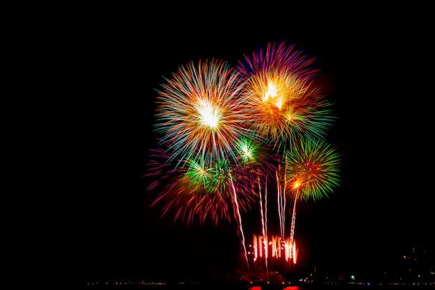 Prachtige kleurrijke vuurwerkshow op het strand, verbazingwekkende feestvuurwerkfeest of een feestelijke gebeurtenis in de donkere hemel.