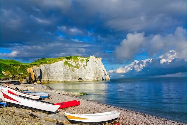 Prachtige kliffen aval van etretat, rotsen en natuurlijke boog landmark van beroemde kustlijn, kleurrijke boten en zee landschap van normandië, frankrijk, europa