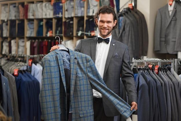 Prachtige knappe man poseren in winkel met jas.