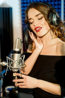 Prachtige knappe vrouwelijke vocale artiest met gesloten ogen zingen in de moderne opnamestudio. portret van een vrij jong model dat in studio zingt.