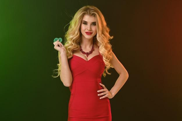 Prachtige krullende blonde vrouw, lichte make-up, in rode passende jurk en ketting. ze glimlacht, toont twee groene chips, hand op taille, poserend op kleurrijke achtergrond. poker, casino. close-up, kopieer ruimte