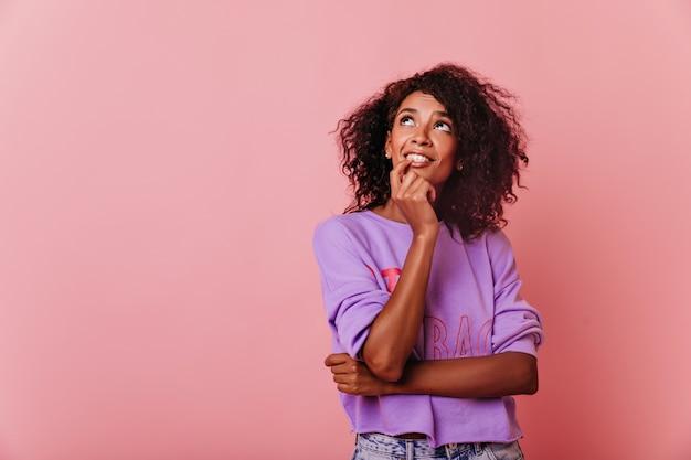 Prachtige krullende brunette vrouw in paars shirt opzoeken. nieuwsgierig stijlvol meisje dat zich op roze bevindt.